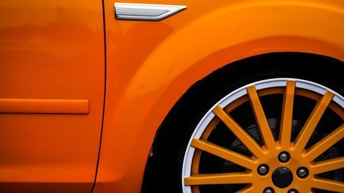 Detail of the front wheel of a yellow car.