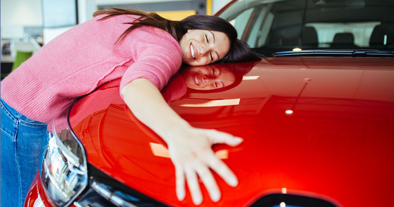 woman smiling and hugging a red car