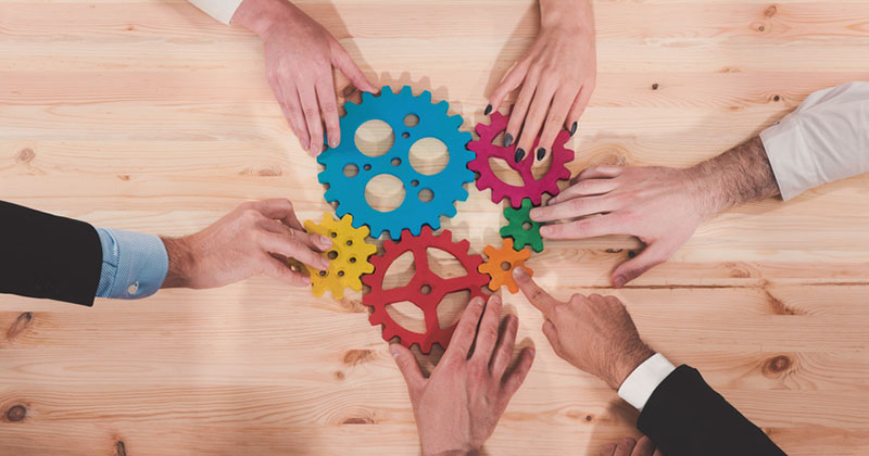 teamwork concept - hands round table holding coloured cogs